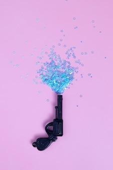 Pistolet jouet vintage avec mini étoiles bleues sur rose