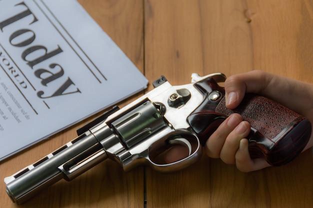 Pistolet à la main avec flou fond doux des billets de banque et des journaux sur table en bois