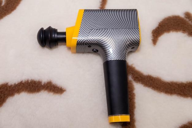 Pistolet de massage à choc thérapeutique professionnel sans fil portable sur une couverture à la maison