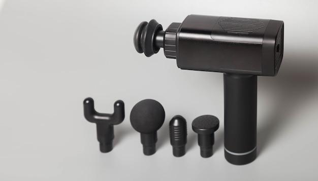Pistolet de massage de choc thérapeutique professionnel sans fil portable sur fond gris. masseur à percussion des tissus musculaires profonds pour sportifs, détend, soulage les douleurs. concept sports et mode de vie sain