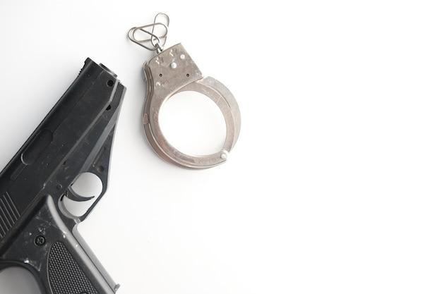 Pistolet et menottes sur fond blanc avec espace de copie.