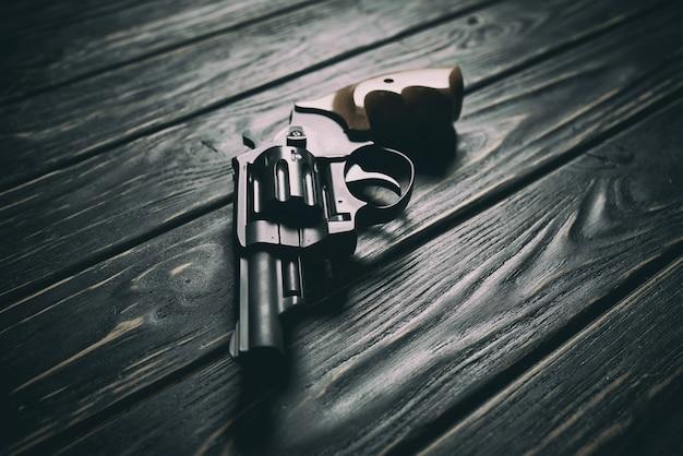 Pistolet revolver sur fond de bois foncé