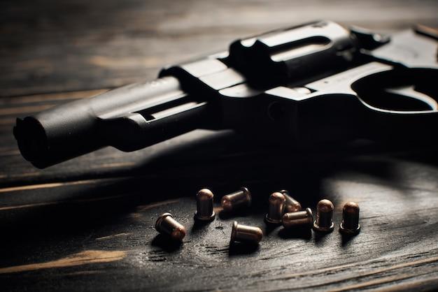 Pistolet revolver avec munitions flobert 4mm sur fond de bois foncé
