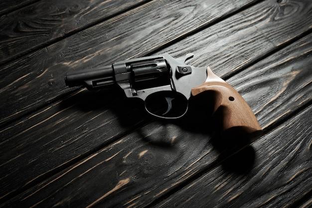 Pistolet revolver noir sur fond de bois foncé