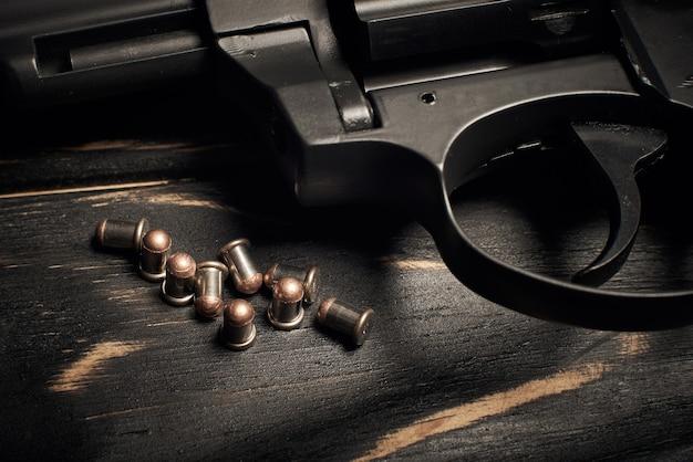 Pistolet revolver noir avec munitions flobert 4mm sur fond de bois foncé