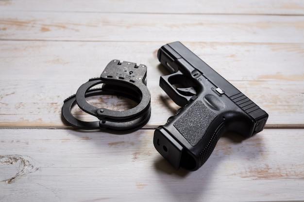 Pistolet semi-automatique noir sur fond de bois ancien.