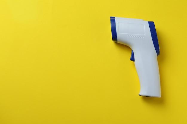 Pistolet thermomètre sur jaune
