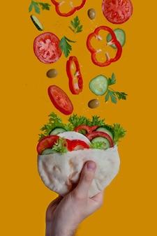 Pita aux légumes dans la main d'un homme