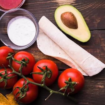 Pita délicieux près de sauce parmi les légumes