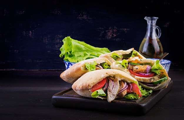 Pita farci au poulet, tomate et laitue sur table en bois. cuisine du moyen-orient.