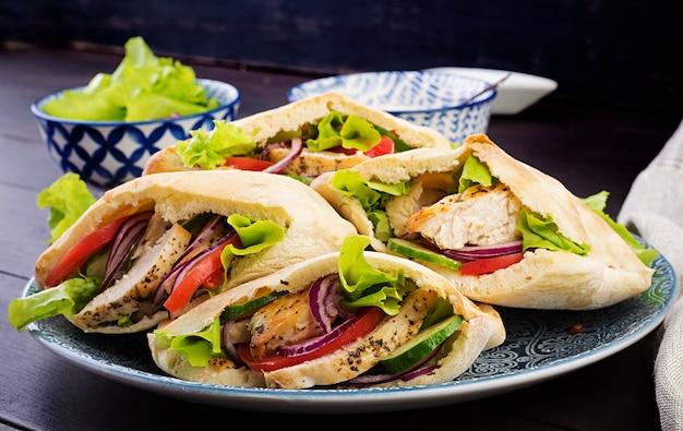 Pita farci au poulet, tomates et laitue dans une cuisine en bois du moyen-orient.