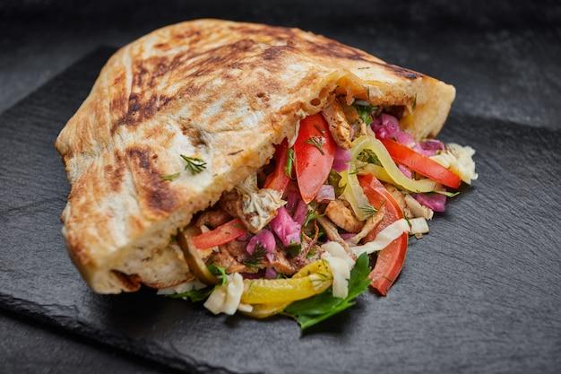 Pita à la viande et légumes, porc, chou, tomates, cornichons, sur ardoise, sur fond noir