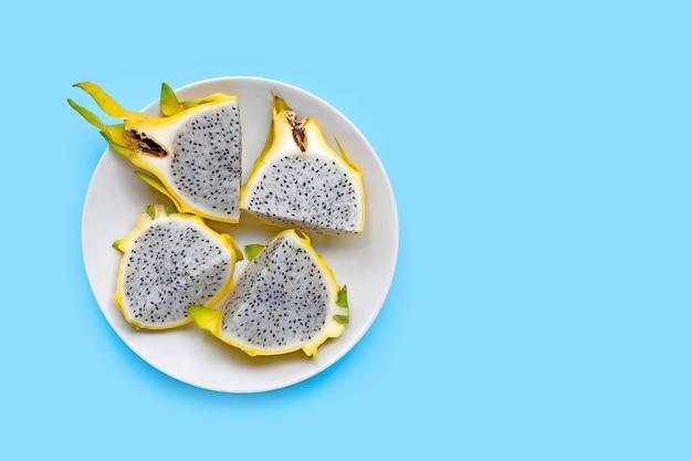 Pitahaya jaune ou fruit du dragon sur plaque blanche sur fond bleu. copier l'espace