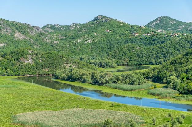 Pittoresque rivière sinueuse coule parmi les montagnes vertes.