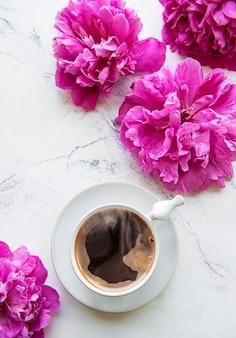Pivoine rose et tasse de café dans un style magnifique sur une surface blanche