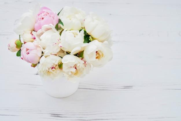 Pivoines blanches dans le pot de fleurs blanches.