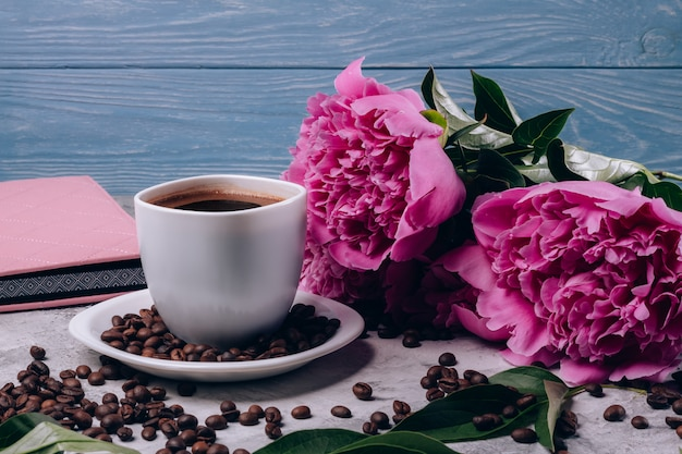 Pivoines avec des boutons roses sur la table à côté du café