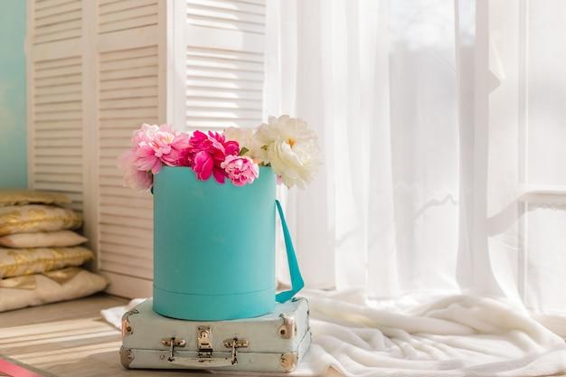 Pivoines roses et blanches dans une boîte en papier. boîte de fleurs. décoration intérieure aux couleurs pastel. bonne fête des mères. carte de voeux floral.
