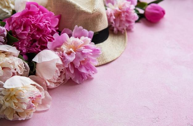 Pivoines roses et chapeau sur un béton rose
