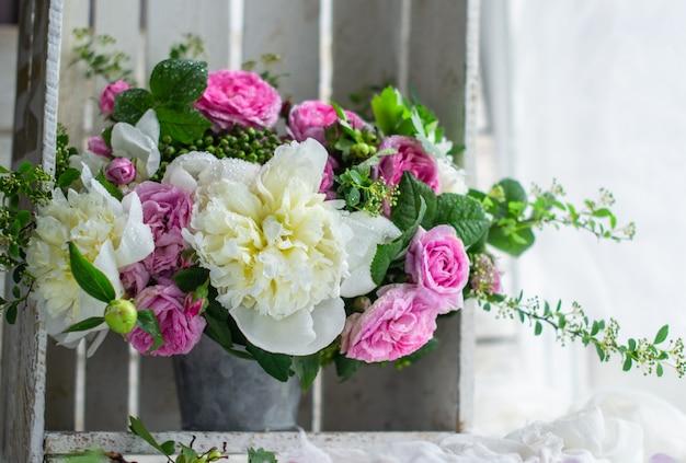 Pivoines et roses dans un vase