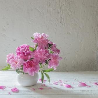 Pivoines roses sur fond vieux mur blanc