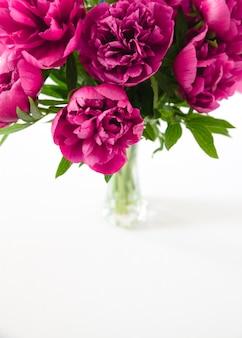 Pivoines rouges dans un vase sur une surface blanche