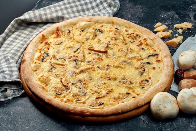 Pizza appétissante avec différents types de champignons, mozzarella et parmesan, sauce blanche. surface sombre. cuisine italienne