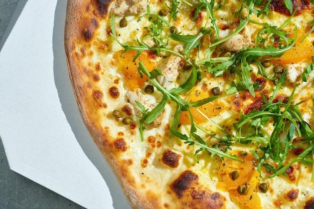 Pizza appétissante avec sauce crémeuse, poulet, tomates jaunes, câpres. côtés croustillants. lumière forte. surface grise.