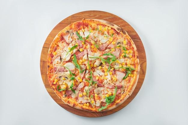 Pizza appétissante avec sauce rouge, jambon, poulet fumé, maïs sur un plateau en bois. fond blanc. cuisine italienne