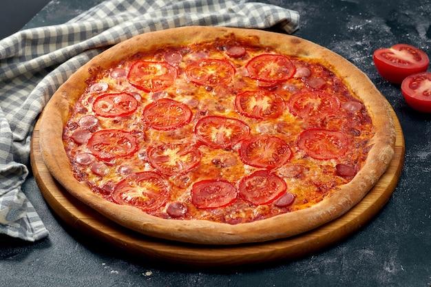 Pizza appétissante avec saucisses au lait, sauce rouge, tomates et fromage. surface sombre. cuisine italienne