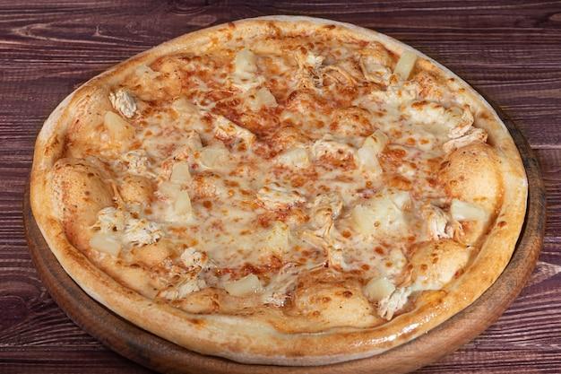 Pizza au bacon et aux herbes sur une plaque en bois avec du fromage et des tomates cerises.