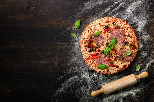 Pizza au basilic, rouleau à pâtisserie, farine sur fond noir foncé, espace copie, vue de dessus