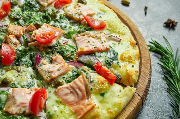 Pizza au four faite maison avec saumon, sauce blanche, épinards, fromage fondu, oignons doux et tomates sur une surface noire dans une composition avec des ingrédients