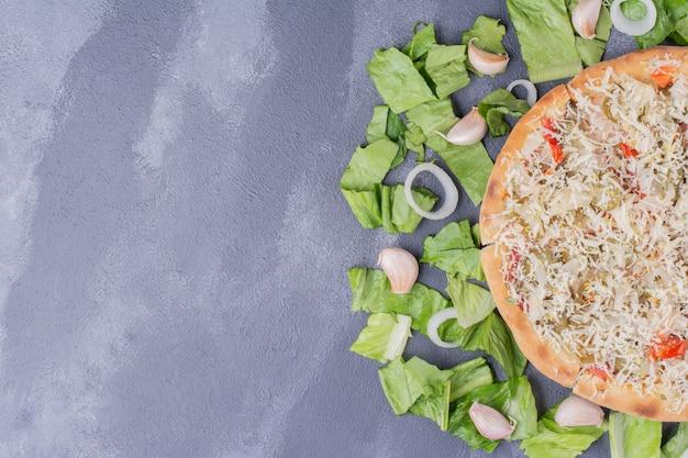 Pizza au fromage au poulet sur bleu avec des légumes frais.