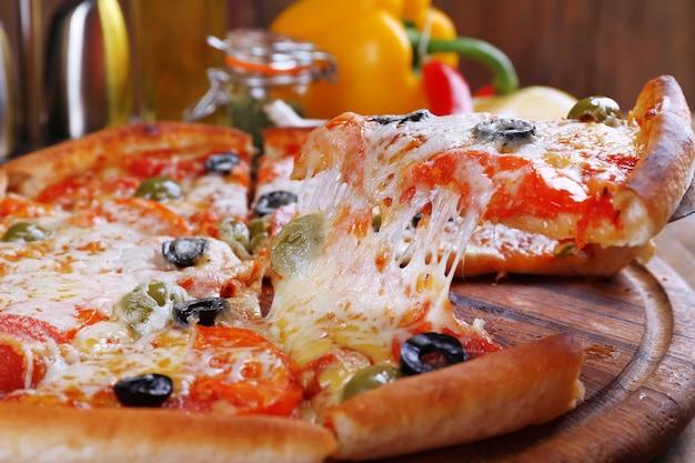 Pizza au fromage à bord et table en bois