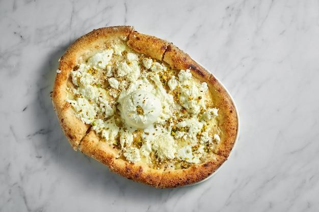 Pizza au fromage à la crème, buratta, sauce à la crème et pistache sur plaque blanche sur marbre blanc