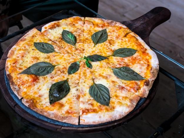 Pizza au fromage avec fusion de feuilles de basilic vue de dessus de style thaïlandais sur la table en bois.