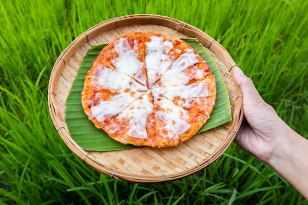Pizza au fromage sur des plaques de tissage traditionnelles en bambou et une feuille de banane à portée de main