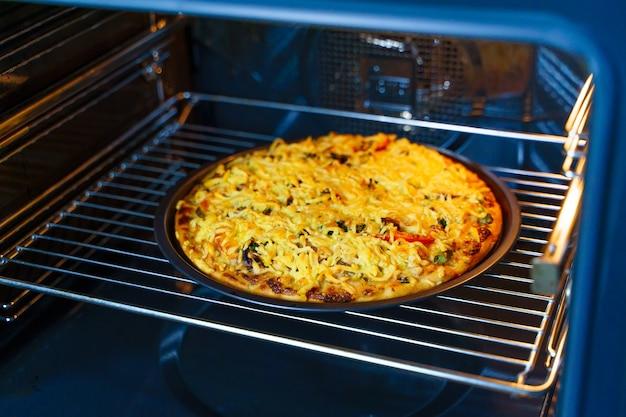 Pizza au fromage sur un plateau rond dans un four. vue horizontale.