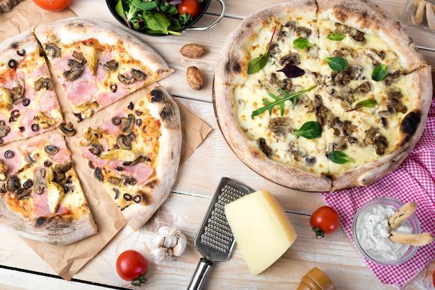 Pizza au fromage; salade au fromage; trempette et légumes sur une surface en bois