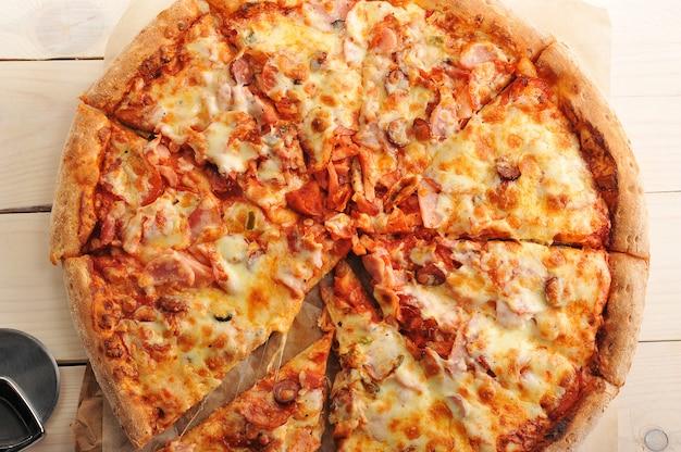 Pizza au fromage et saucisse épicée coupée en tranches