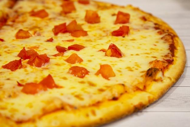 Pizza au fromage et tomates, cuisine italienne, sur fond de bois clair