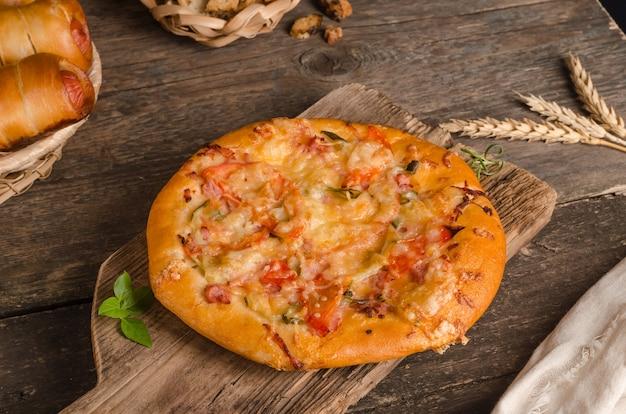 Pizza au fromage et tomates sur un fond en bois avec des ingrédients, restauration rapide