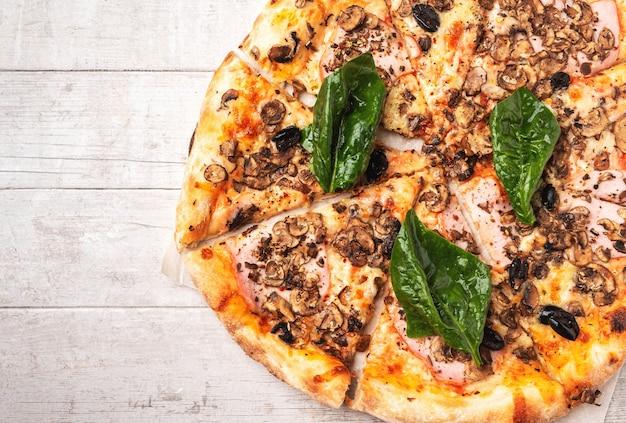 Pizza au jambon et aux champignons sur une table en bois blanche.