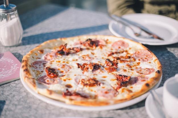 La pizza au jambon et aux tomates marinées servie sur un plat est sur la table du restaurant