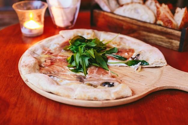 Pizza au jambon de parme nappée de roquette sur une assiette en bois arrondie.