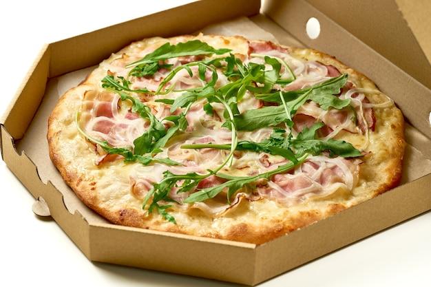 Pizza au jambon et roquette, sauce et fromage fondu, côtés croustillants isolés sur fond blanc