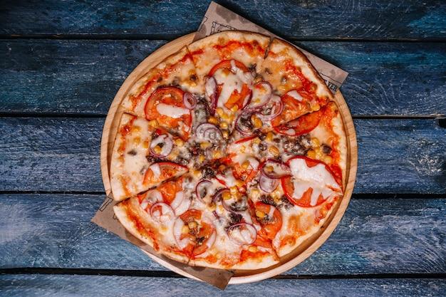 Pizza au maïs, viande et tomates sur fond de planches