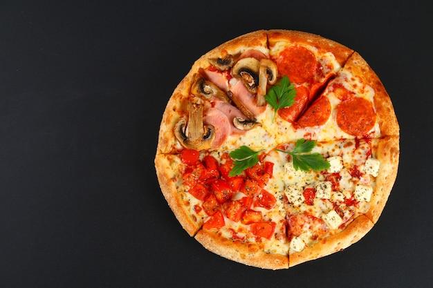 Pizza au pepperoni, champignons, tomates et fromage. quatre goûts dans une pizza. tableau noir.