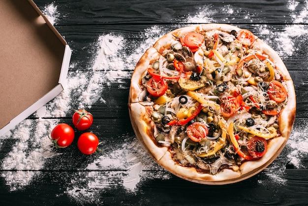 Pizza au pepperoni à côté d'une boîte pour emballer la farine renversée sur une table en bois noir